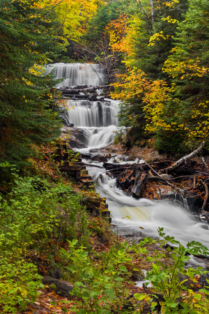 upper peninsula: Sable Falls, a waterfall in Upper Peninsula Michigans Pictured Rocks National Lakeshore, is surrounded by fall color and evergreen trees.
