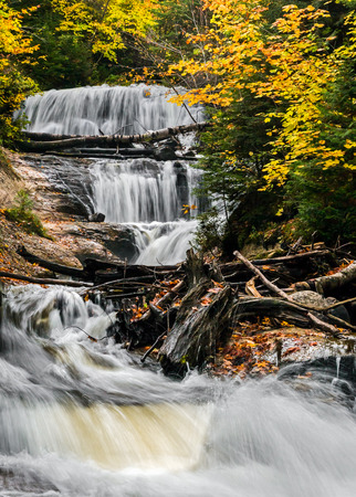 pictured: Sable Falls, a waterfall in Upper Peninsula Michigans Pictured Rocks National Lakeshore, cascades through an autumn landscape of boulders and fallen trees.