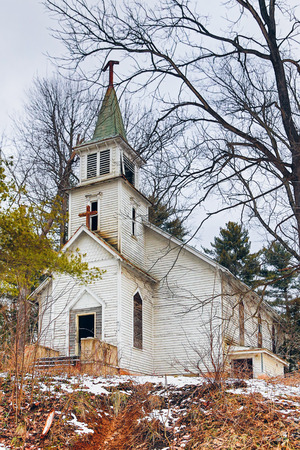 An old abandoned white church building withers away in a rural setting.