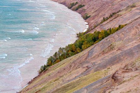 pictured: The Grand Sable Dunes, seen here in the light of an early autumn morning, steeply rise from the shore of Lake Superior near Grand Marais, Michigan in Pictured Rocks National Lakeshore park. Stock Photo