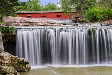 cataract falls: Upper Cataract Falls, a scenic waterfall in Indiana, is topped by a red historic covered bridge.