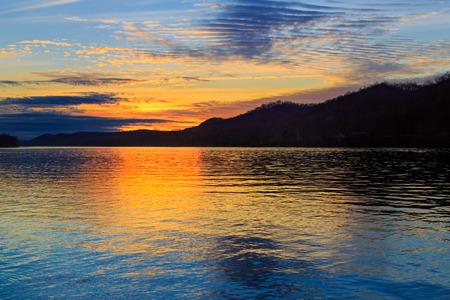 석양 silhouettes 언덕 그것으로 Paden 도시, 웨스트 버지니아에서 본 오하이오 강 바다에 반영합니다.