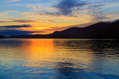 The setting sun silhouettes hills as it reflects upon the waters of the Ohio River as seen from Paden City, West Virginia.