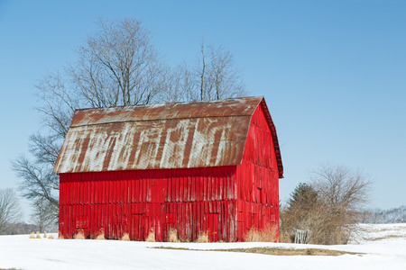 A vivid red wooden barn is topped with a rusty metal roof in a snowy landscape under a clear blue sky.