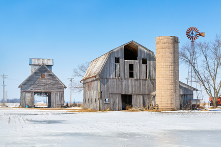 wood agricultural: Old barns with a silo and windmill stand in a snowy Indiana landscape.