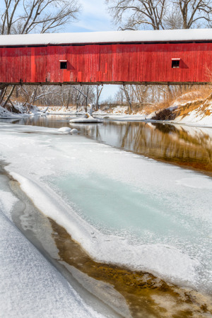 frozen creek: The historic red Oakalla Covered Bridge crosses a snowy and  partially frozen Big Walnut Creek in rural Putnam County Indiana .