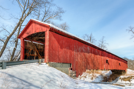 The historic red Oakalla Covered Bridge crosses Big Walnut Creek in rural Putnam County Indiana. photo