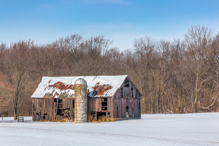 An old and dilapidated barn and silo stand in a snowy landscape on a clear and sunny day. photo