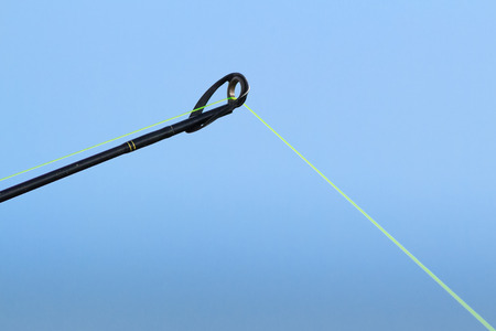 Fishing pole: The tip of a fishing pole with line is photographed close against a blue sky.