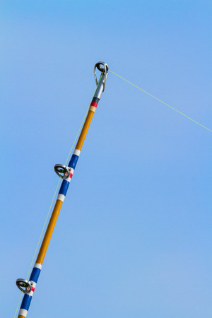 Fishing pole: A fishing pole with fishing line is photographed in action with a blue sky backing.
