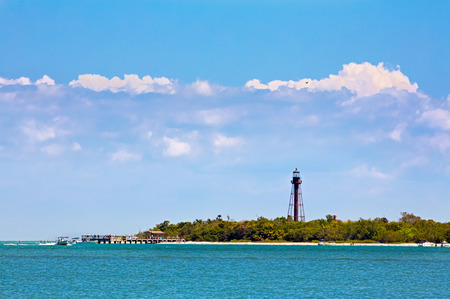 navigational light: People on a pier, boats, and a sandy beach are backed by the brown metal tower of Florida