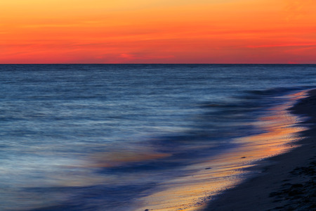 gulf of mexico: A dramatic sunset sky glows above the sea, photographed with a long exposure for a dreamy, surreal look. Shot on the Gulf of Mexico at Sanibel Island, Florida.