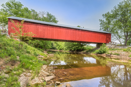 covered bridge: The historic red James Covered Bridge crosses Big Graham Creek in rural Jennings County Indiana. Stock Photo