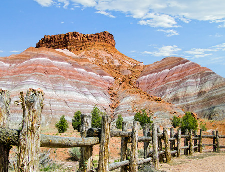 vividly: Vividly colorful striated cliffs rise behind a rustic fence in the western landscape of southern Utah desert near Pahreah. Stock Photo
