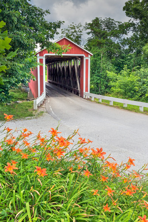 covered bridge: Orange roadside lilies bloom near a red covered bridge in rural Franklin County, Indiana. Enochsburg Stock-heughter Covered Bridge.