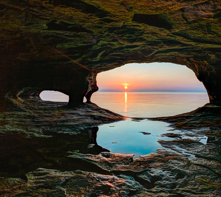 alger: The sunset over Lake Superior is viewed from a secluded and remote sea cave along Michigans northern coast.