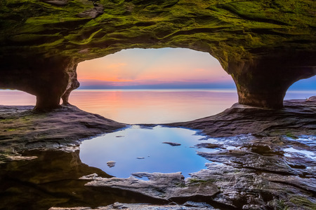 alger: A colorful sunset sky over Lake Superior is photographed from within a sea cave on Michigans northern coast near Pictured Rocks National Lakeshore.