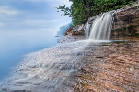 elliot: Elliot Falls, a small but beautiful waterfall on Miners Beach at Michigans Pictured Rocks National Lakeshore, spills over rock ledges and into Lake Superior after sundown.