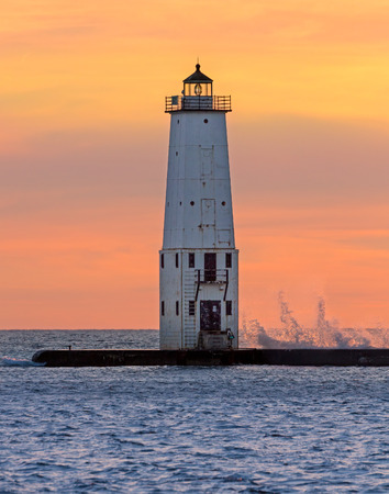 lake michigan: The Frankfort North Breakwater Lighthouse stands against a vivid suset sky with breaking waves on Lake Michigan.