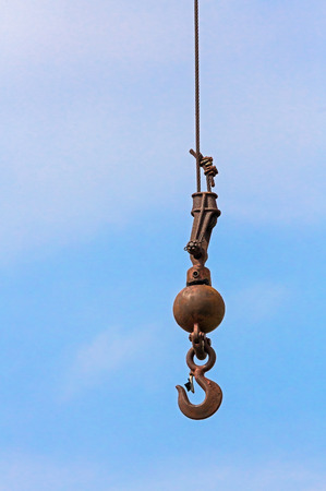 jib: A cranes hook hangs from a thick cable against a cloudy blue sky.