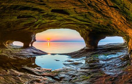 호수 슈퍼의 차가운 물에 반사 된 석양은 북부 미시간의 어퍼 반도의 해안을 따라 바다 동굴에서 볼 수 있습니다.