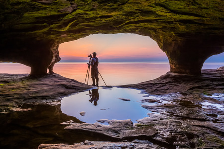 alger: A photographer with tripod, standing in the mouth of a Michigan sea cave, is silhouetted by a colorful sunset over Lake Superior.