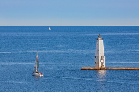 lake michigan lighthouse: The Lighthouse on Lake Michigan at Frankfort, Michigan is photographed with sailboats from a bluff to the south overlooking the town.