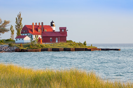 The lighthouse and fog horn building at Point Betsie stand on Michigans Lake Michigan coast in the glow of the setting sun.