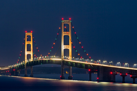 Colorful lights decorate the Mackinaw Bridge, a long suspension bridge and engineering marvel crossing the Straits of Mackinac and connecting Michigans Upper and Lower Peninsulas.