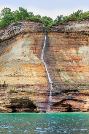pictured: Bridal Veil Falls, a tall, slender waterfall in Michigans Pictured Rocks National Lakeshore, cascades down a colorful cliff and into Lake Superior.