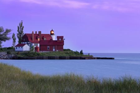 lake michigan lighthouse: Michigans Point Betsie Lighthouse shines its light over Lake Michigan at sundown.