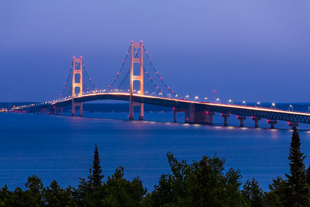 The Mighty Mackinac Bridge, connecting Michigan's Upper and Lower Peninsulas, carries vehicles over waters flowing from Lake Michigan and into Lake Huron.
