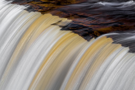 Tannin-stained whitewater pours over the brink of Upper Peninsula Michigans Tahquamenon Falls, the second largest waterfall east of the Mississippi.