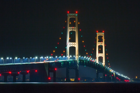 mackinac: Light on the mighty Mackinac Bridge shine in the darkness as vehicles travel between Michigans Upper and Lower Peninsulas. Stock Photo