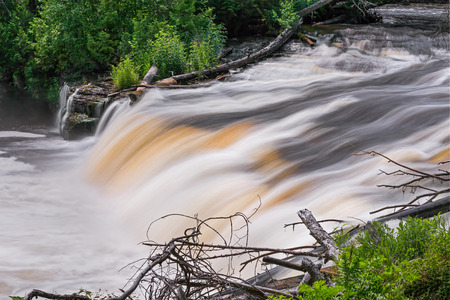 upper peninsula: Tannin-stained whitewater cascades over rocks at Lower Tahquamenon Falls in the woods of Upper Peninsula Michigan.
