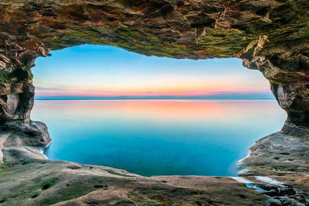 alger: A sunset sky, reflected upon a calm Lake Superior, is framed by a sea cave along the Upper Peninsula coastline of Michigan. Stock Photo