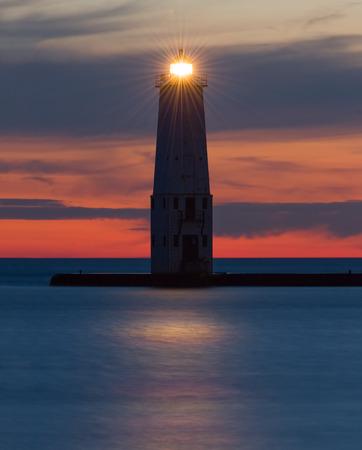 lake michigan lighthouse: El hist�rico de Frankfort, Michigan faro brilla silueteado por un cielo colorido atardecer sobre el lago Michigan.
