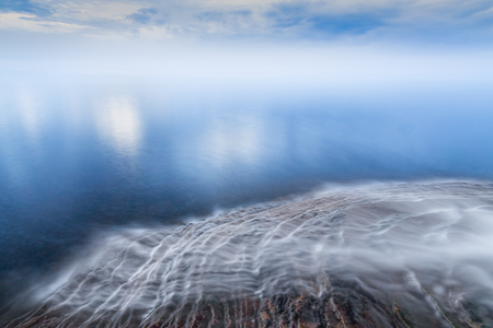 elliot: Water flows over the sandstone ledges of Michigans northern coast and into Lake Superior with a cloud-draped horizon. Elliot Falls is in Pictured Rocks National Lakeshore near Munising, Michigan.