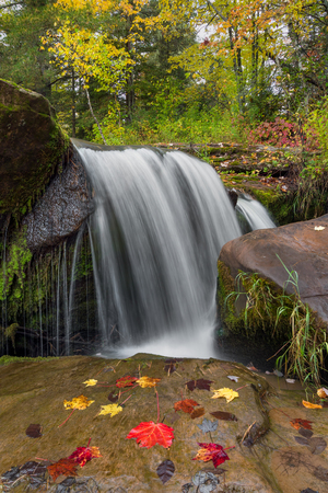 cataract falls: Whitewater plunges over a  rock ledge with colorful autumn leaves at the upper cataract of O Kun De Kun Falls, a waterfall in the scenic Upper Peninsula of Michigan. Stock Photo