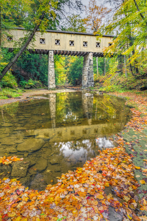 yesteryear: The historic Windsor Mills Covered Bridge, Wiswell Road Bridge or Warner Hollow Road Bridge, crosses Phelps Creek with colorful autumn leaves in rural Ashtabula County, Ohio.