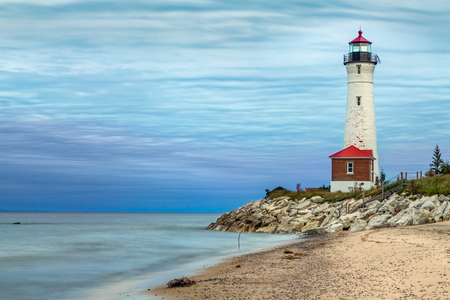 blustery: The historic Crisp Point Lighthouse, photographed here at sunset on a cloudy day, has stood for over a century in the Lake Superior coast of Upper Peninsula. Stock Photo