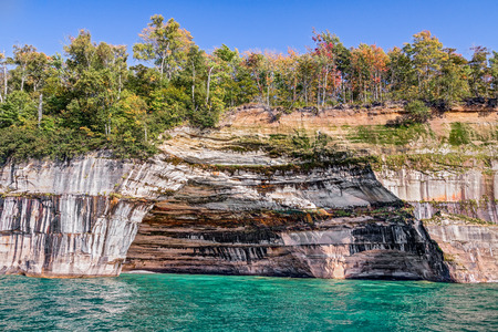 alger: A large rock alcove adorns the cliffs at Pictured Rocks National Lakeshore on the Upper Peninsula Michigan Coast of Lake Superior. Stock Photo