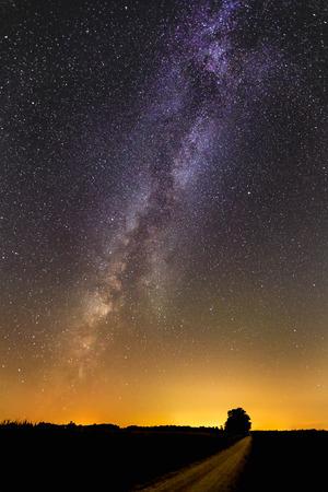 La Vía Láctea pinta el cielo de la noche sobre una carretera nacional en zona rural de Indiana en una noche de verano.