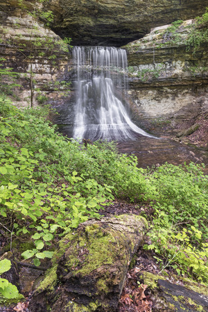immediately: Water flows from Porter Cave and immediately tumbles over steep waterfall in rural Indiana.