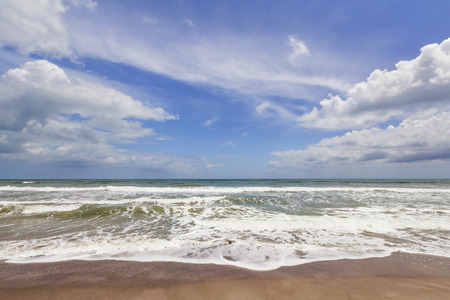 cocoa beach: Waves break gently on a sandy beach with beautiful clouds in a deep blue sky over aqua waters.