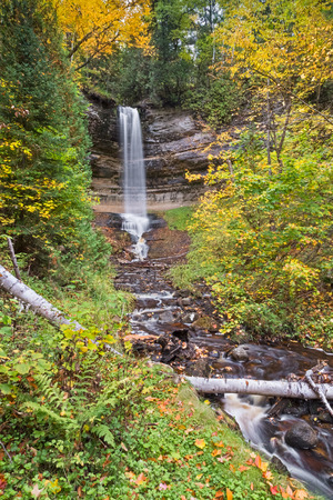 alger: Colorful fall foliage surrounds Munising Falls, a waterfall in Upper Peninsula Michigans Pictured Rocks National Lakeshore.