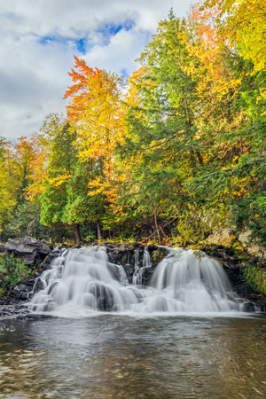 powerhouse: Colorful autumn leaves and a cloudy blue sky top Upper Peninsula Michigans Power House Falls on the Falls River near LAnse.