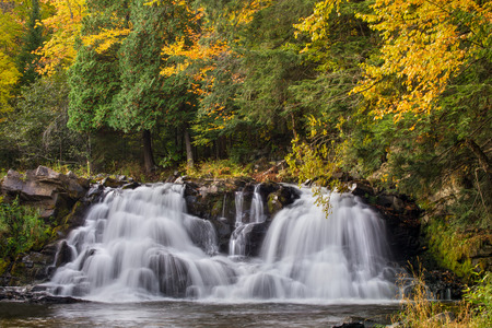 powerhouse: Powerhouse Falls, a waterfall on Michigans Falls River, cascades down rocks surrounded by autumn foliage. Stock Photo