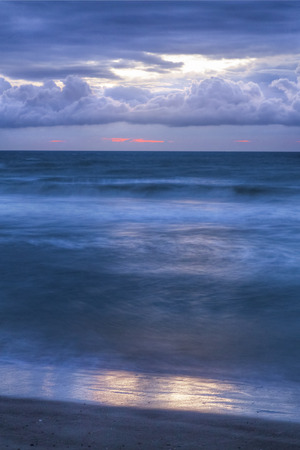 cocoa beach: Breaking waves are photographed with a long exposure beneath a colorful and dark sunrise sky over the Atlantic Ocean.