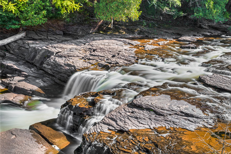 Presque Isle River whitewater flows over Upper Peninsula Michigan's Manido Falls, a waterfall in Porcupine Mountains Wilderness State Park.